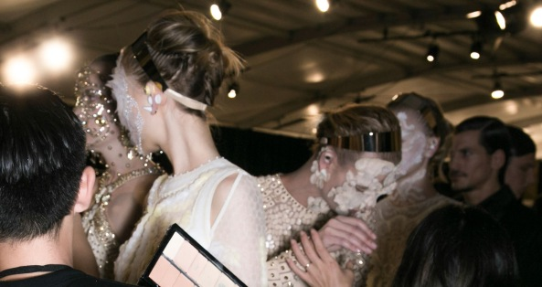Models preparing to walk at Givenchy in Tisci's lace and pearl face masks.