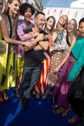Models hugging designer Jonathan Saunders backstage